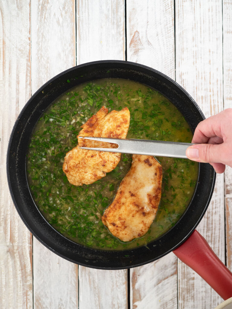 placing cooked chicken fillets back in the pan with lemon sauce