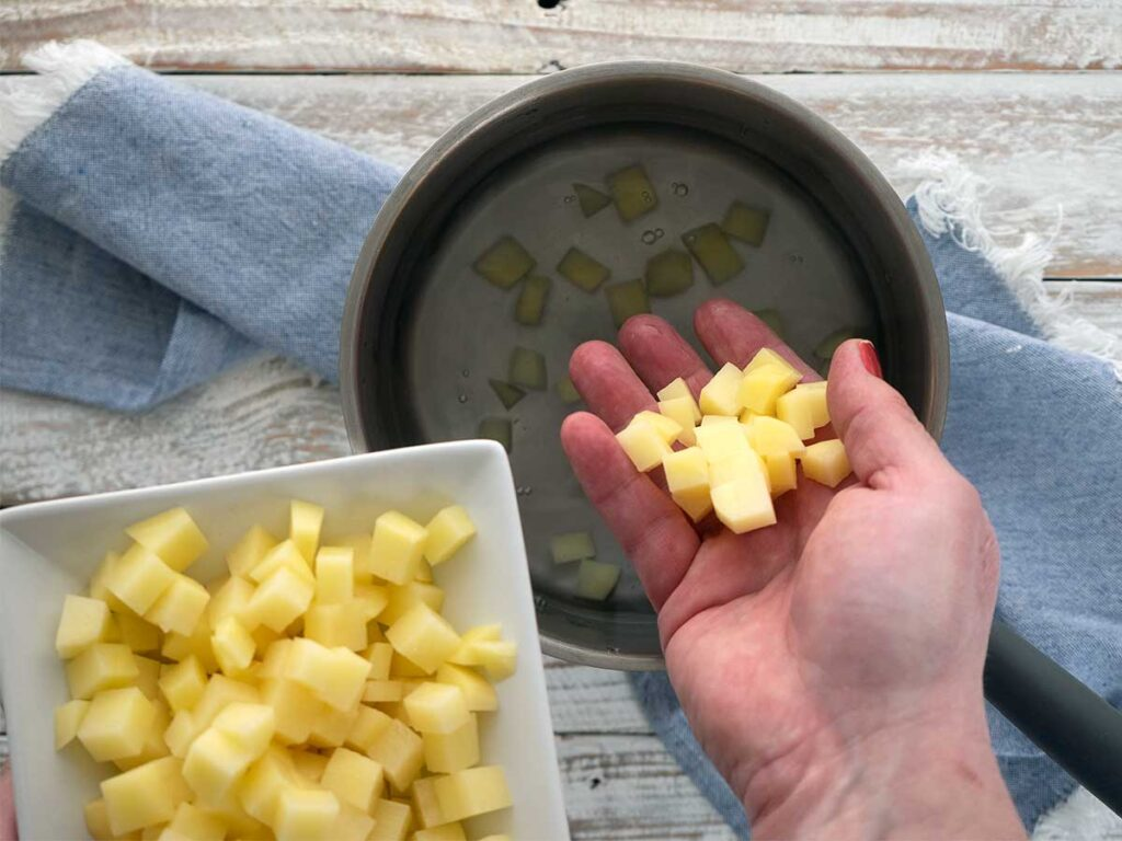 placing diced potato into a saucepan