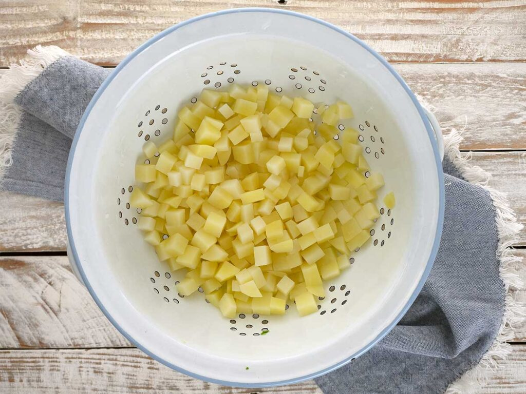 cooked diced potato in a white colander