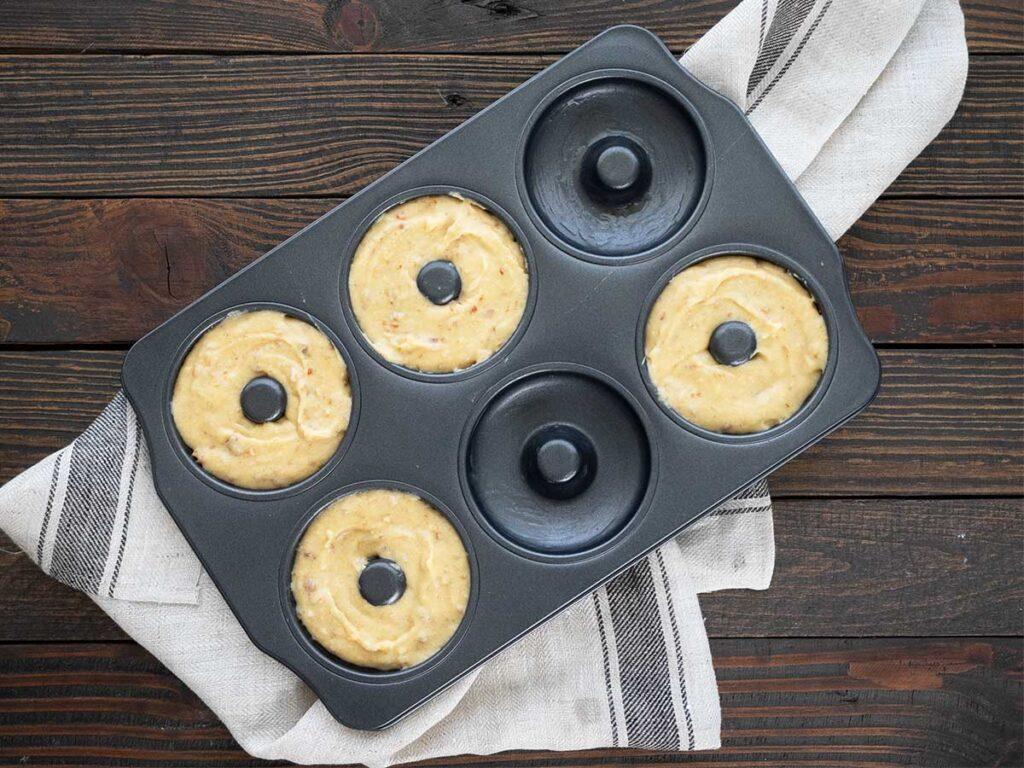 date donut batter in donut tin ready to bake