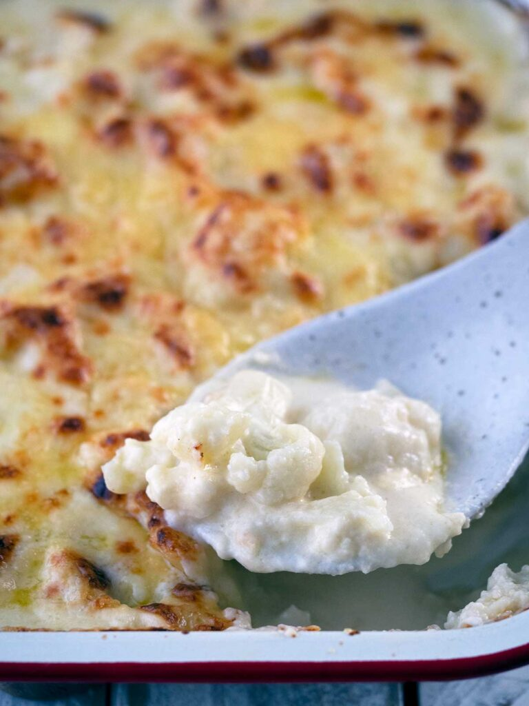 close up image of cheesy cauliflower on a serving spoon