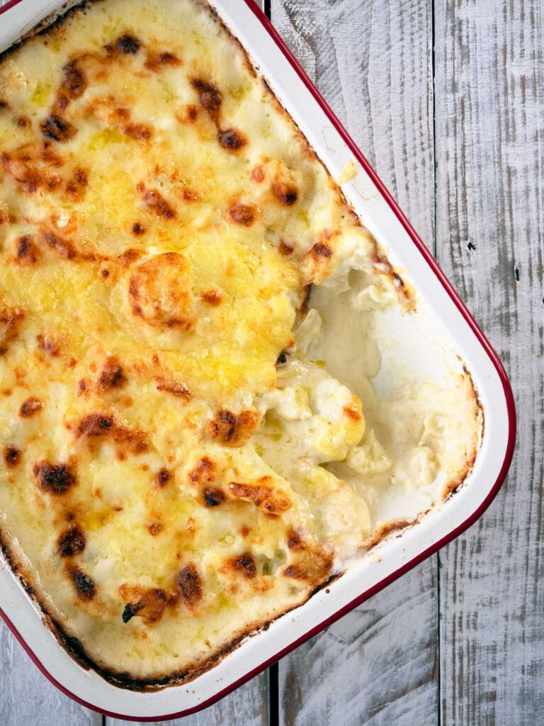 baked cheesy cauliflower in a pan with a spoonful missing