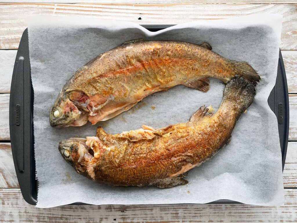 cooked rainbow trout on a lined baking tray