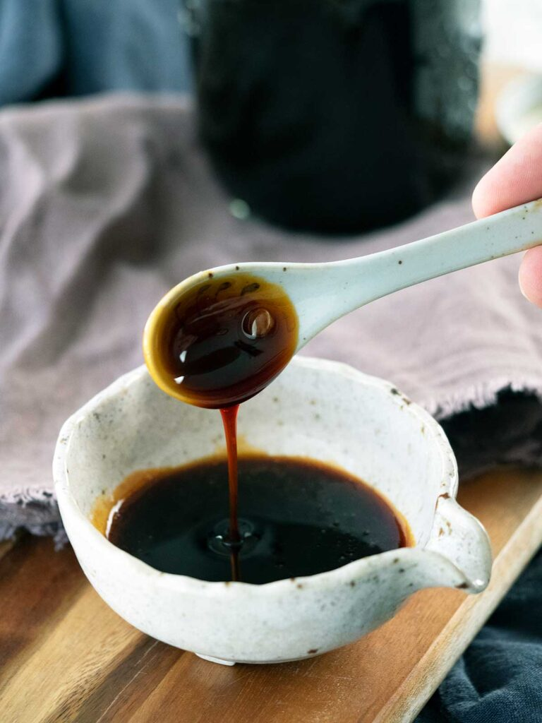 a spoon dripping teriyaki sauce into a pouring bowl