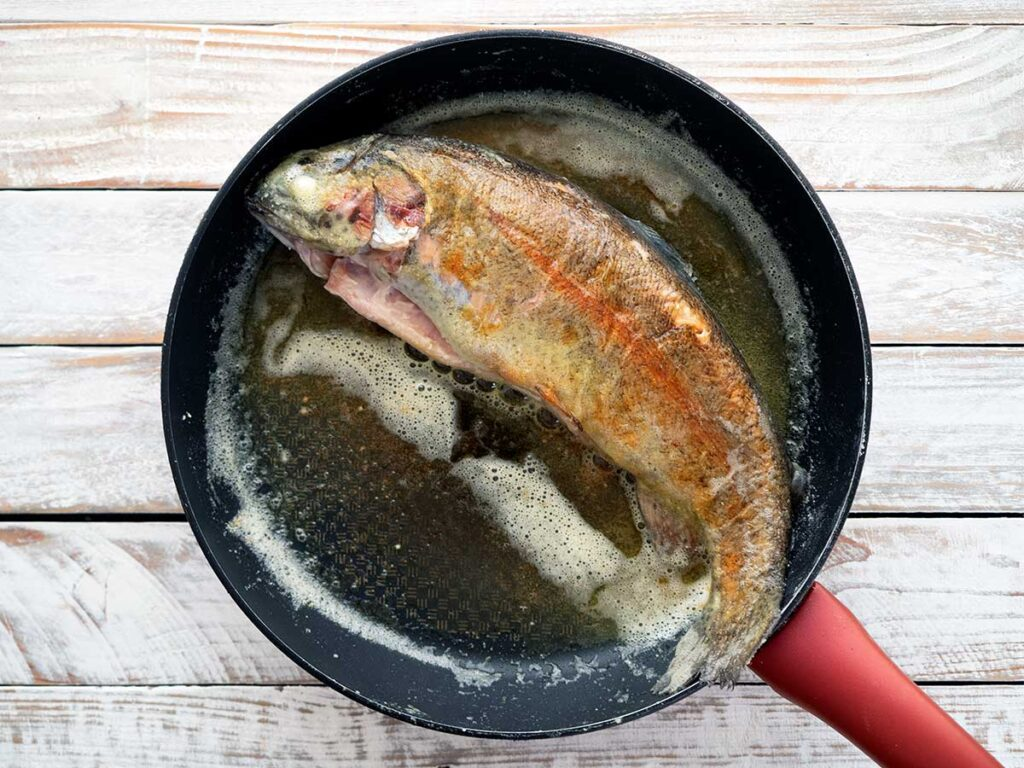 browning a whole rainbow trout in a frying pan