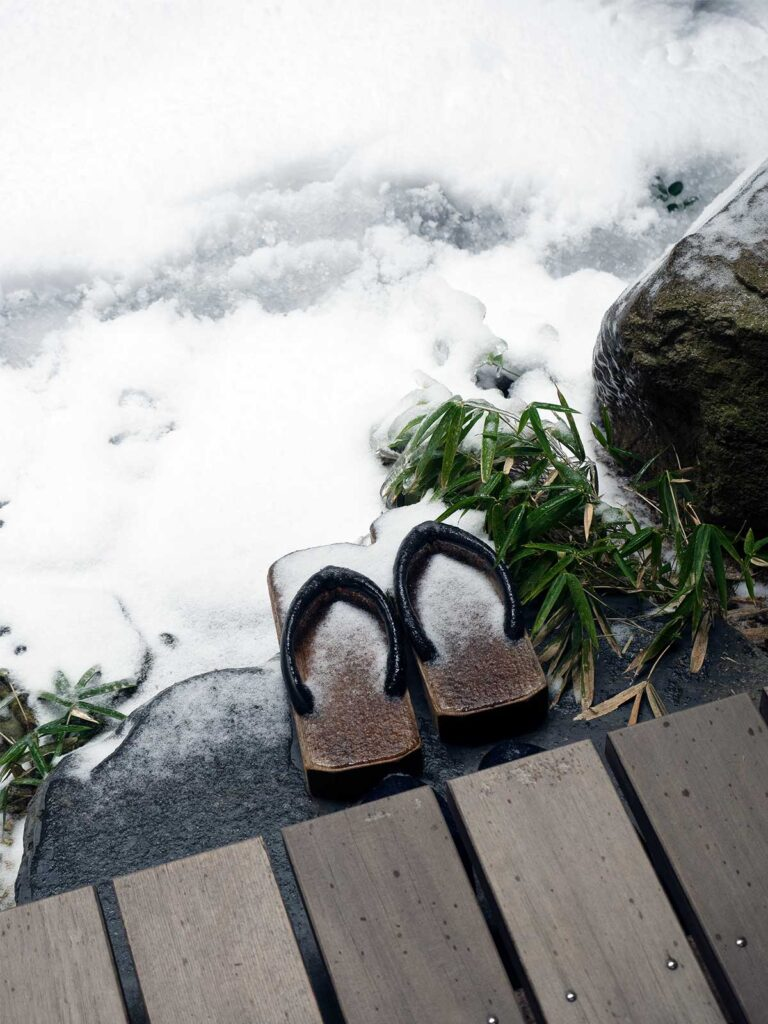 a pair of geta (japanese traditional wooden shoes) in the garden covered in snow